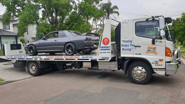 An older car being towed in a quiet Sydney suburb