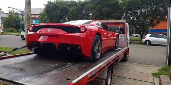 A Ferrari getting towed from a quiet Sydney suburban street on an overcast day.